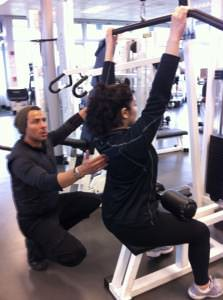 Personal trainer assisting with form on weight training exercise