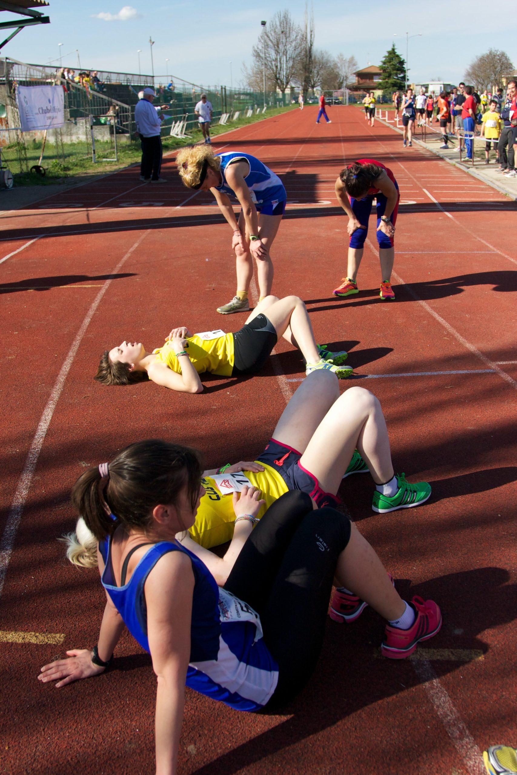 women finishing run race lay on run track exhausted